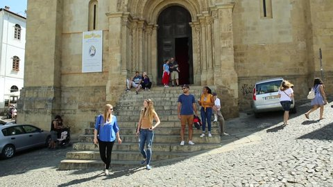 Coimbra, Portugal - August 14, 2017: tourists in front of Old Coimbra Cathedral. Se Velha de Coimbra, is one of most important romanesque buildings in Central Portugal in university town of Coimbra.