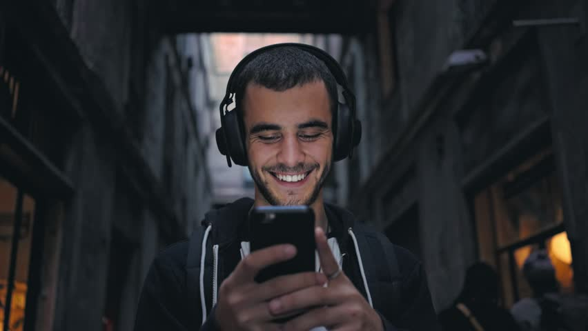 Smiling and laughing handsome young man listening music from his smartphone in wireless black headphones, dancing on street of old town center in europe at twilight or evening time | Shutterstock HD Video #32030479