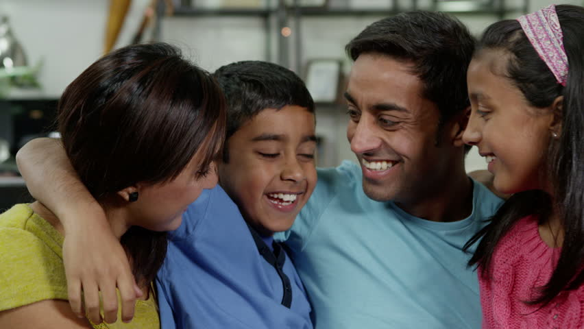 Happy family of 4 seated together at home. They are laughing and hugging. | Shutterstock Video #3204121