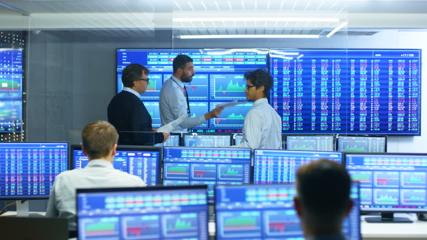 Three Experienced Stock Traders Talking Business, Consulting Documents and Argue About Data. They Work for a Big Stock Exchange Firm. Office is Full of Displays Showing Infographics and Numbers. | Shutterstock HD Video #32060707