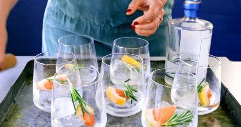 Party hostess preparing cocktails for her guests at a party, a tray of gin vodka mixed drinks