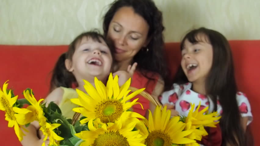 A woman with children and a basket of flowers of sunflowers. Happy mother with children and sunflower.   Shutterstock HD Video #32073517