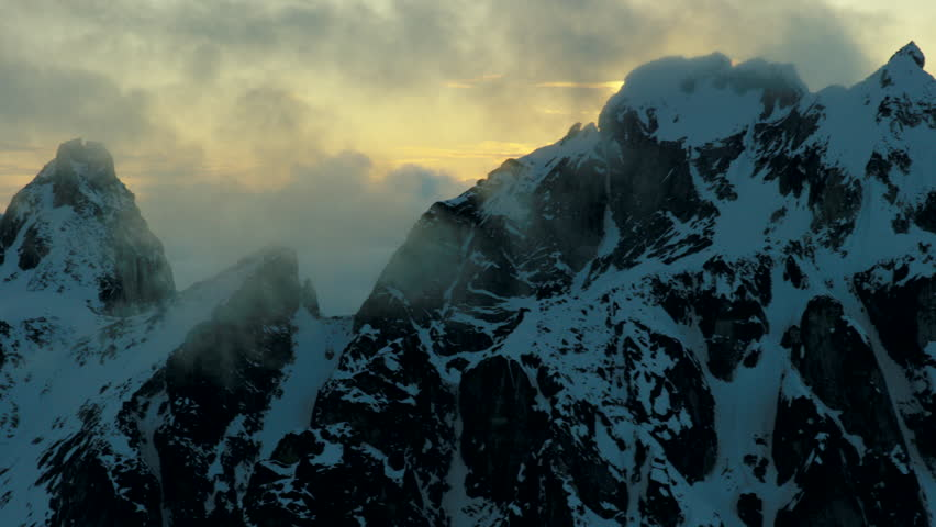 Stunning aerial footage of the sunsetting behind low clouds above the Alaska mountains, as seen through a jagged alpine ridge.