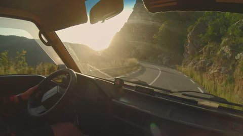 View from inside old retro camper van moving on curvy serpentine muntain roads at sunset, escaping to nature for great adventures concept