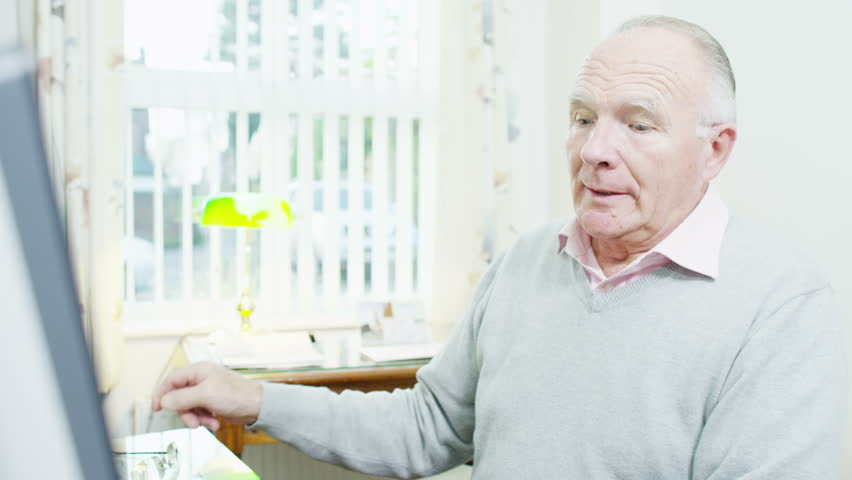 A senior gentleman is using his computer at home on a bright autumn day | Shutterstock HD Video #3208327