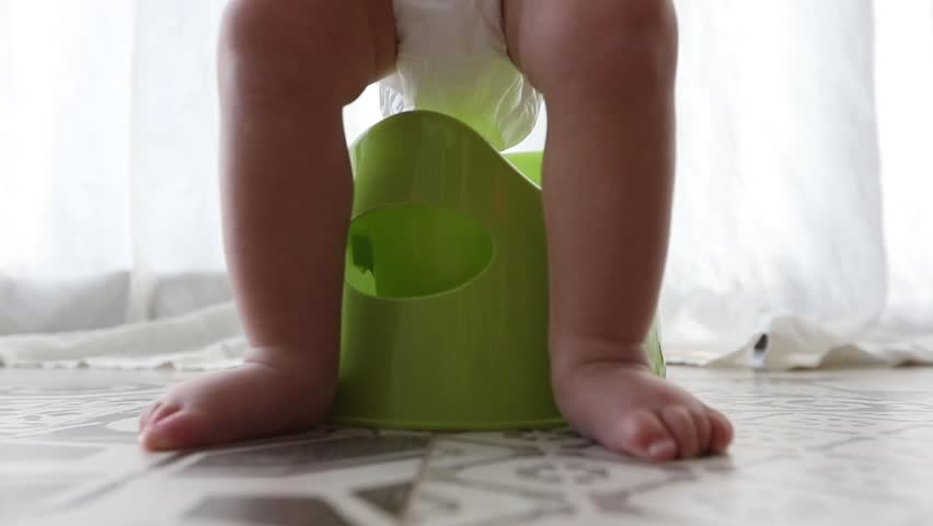 Baby sitting on chamberpot, Children's legs hanging down from a chamber-pot. Toddler gets up from the pot with a close-up only legs