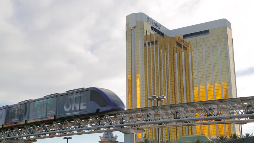 Las Vegas, Nevada - April 2017: Las Vegas monorail train traveling high near the Mandalay Bay hotel and casino. The golden facade of Mandalay Bay sparkles in the rays of the sun. Landscape Las Vegas. | Shutterstock HD Video #32107597
