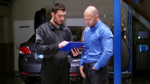 auto service, repair, deal and people concept - mechanic and customer or car owner signing paper shaking hands at workshop