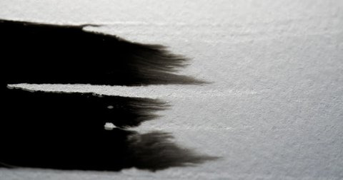 Black ink bleeding on white paper in amazing detail
