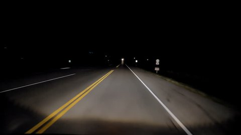 Driving an old country highway in the dead of night in the middle of nowhere with little traffic after sunset with no stars, no moon and little light on a yellow lined back road somewhere in Kentucky.
