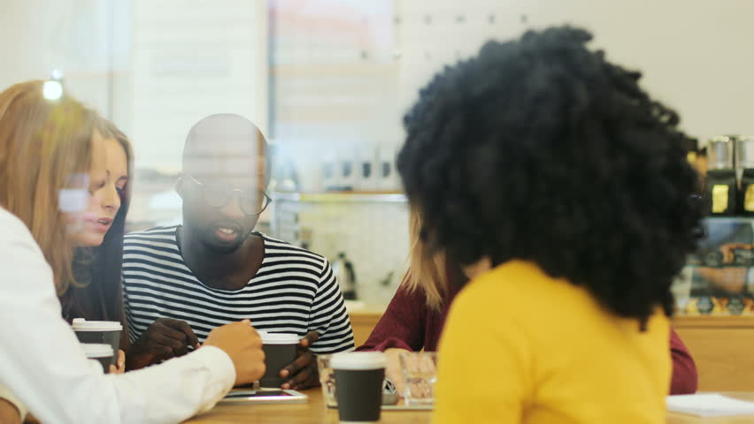 Close up window view of a young diverse group of groupmates discussing different issues while drinking coffee in the restaurant   Shutterstock HD Video #32123638