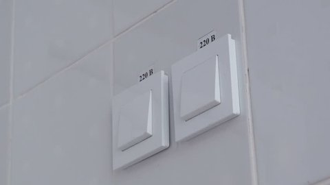 Switching on and off the light switch on the wall. White switch on a white wall with the inscription 220 volts. Man's hand presses the switch.