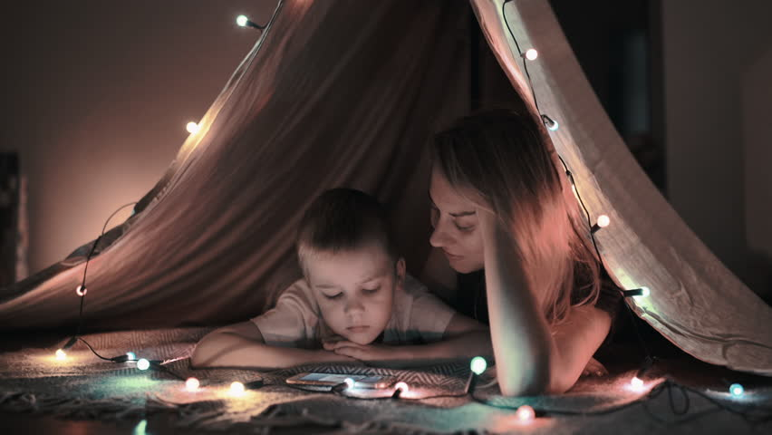 Mother and son play and watching smartphone in children's room in tent with Christmas decorations