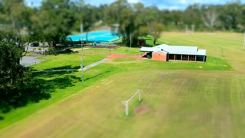 Drone flight park ride on lawn mower tiny town. club house, swings and netball courts on a beautiful day