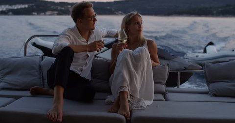 Young Couple Talk, Drink Champagne in the Stern of the Moving Yacht. They Have Great Romantic Evening. In the Background Island with Small Village. Shot on RED Epic 4K UHD Camera.