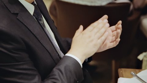 Man clapping sitting at a table in a restaurant. Close-up of hands