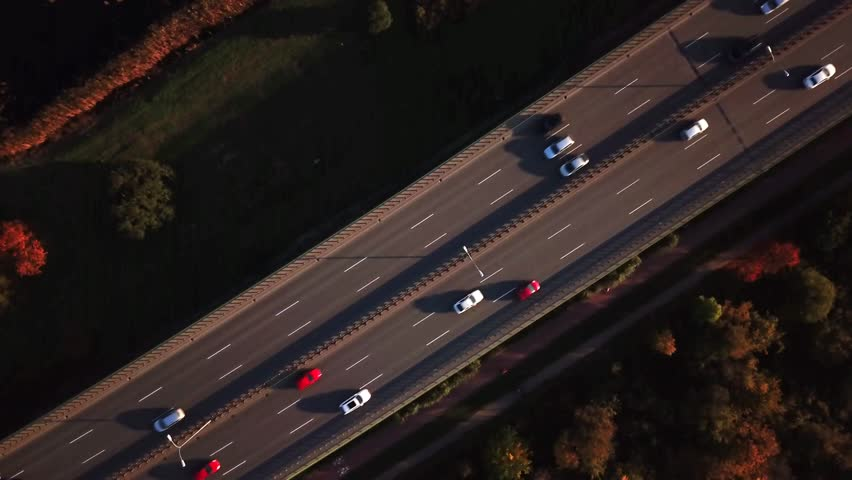 4K AERIAL: Cars and semi truck driving on busy highway across the country in beautiful autumn evening. People on road trip traveling on busy freeway at golden sunset #32186047