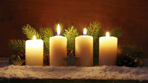Four white Advent candles with christmas decoration.