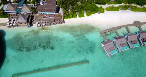 v09417 five 5 star resort water bungalows in Maldives with drone aerial flying view on white sand beach on tropical island