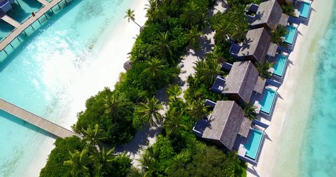 v09545 five 5 star resort water bungalows in Maldives with drone aerial flying view on white sand beach on tropical island