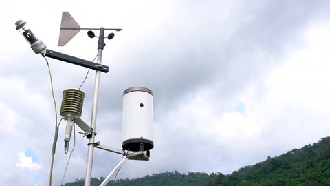 Meteorological weather station antenna with meteorology sensors, pale overcast cloudy sky and forest in background. Weather station for background.