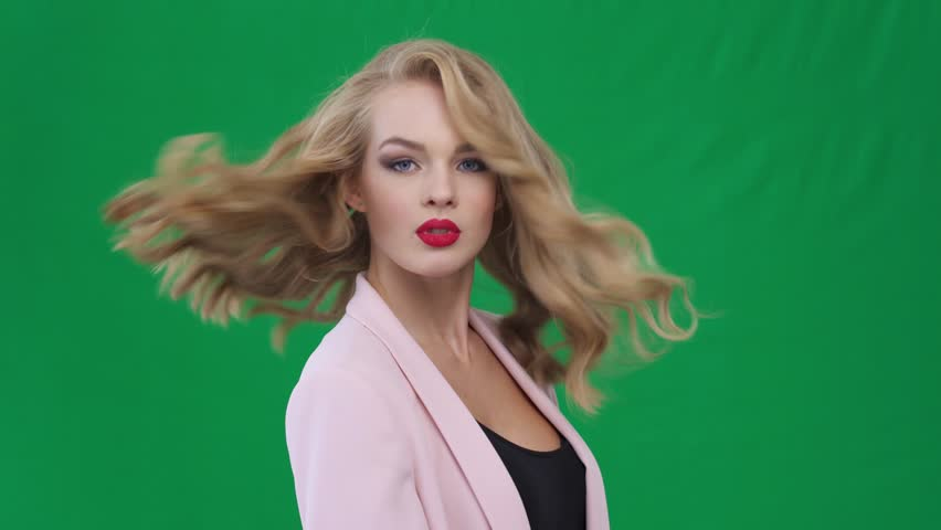Closeup face of beautiful blond sexy smiling girl with long hair. Attractive young smiling woman looking at camera over green screen.