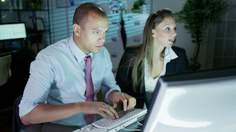 A businessman and businesswoman are working late at night in a room full of computers. They are looking at the screens in front of them and discussing their work