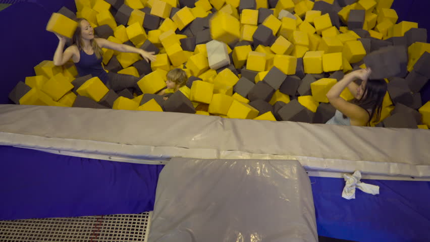 Two young women and a boy having fun with soft blocks at indoor children playground in the foam rubber pit in the trampoline center. | Shutterstock HD Video #32206057