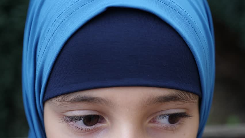 portrait of a modest girl, a Muslim wearing a hijab looks at the camera, 4k, slow-motion. copy space