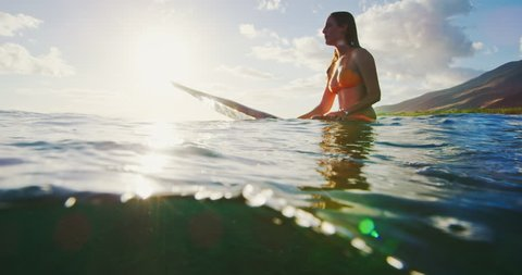 Beautiful young woman surfing at sunset