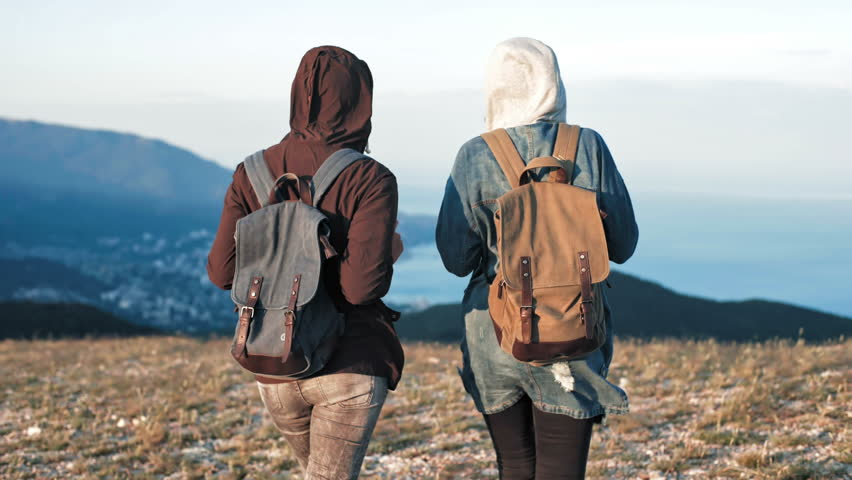 Two young women tourist with backpack walking at rock of mountains with beautiful nature landscape at background | Shutterstock HD Video #32258917