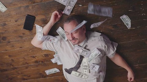 Businessman lying on the floor dancing with a lot of money.
