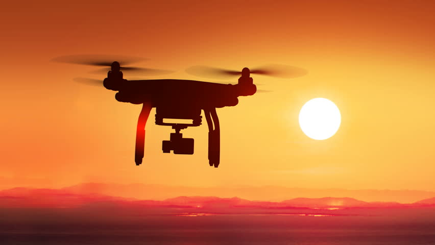 Quadcopter Flying Far Away to the Beautiful Sunset Sun. Modern Electronics Concept. 4k UHD 3840x2160.