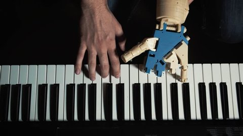 Robot plays a musical instrument. man musician pianist with a prosthetic hand playing the piano. He plays with two hands, a robot and a human hand. Robot creates music and art.