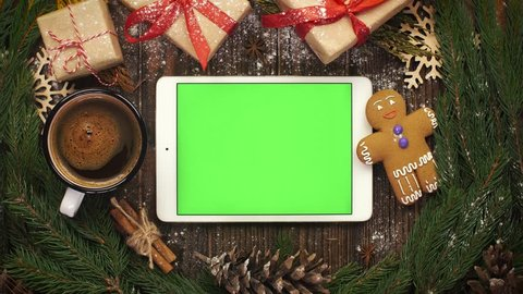 Look from above at tablet with green screen lying among Christma