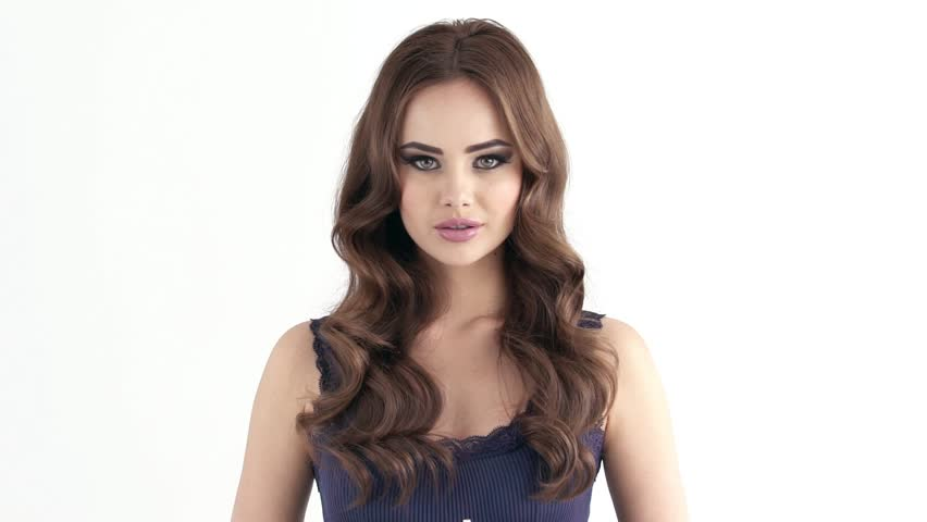 Beautiful  sexy girl with long flyaway hairs. Attractive young woman with pretty face and wave brown hairstyle -  looking at camera. Slow motion