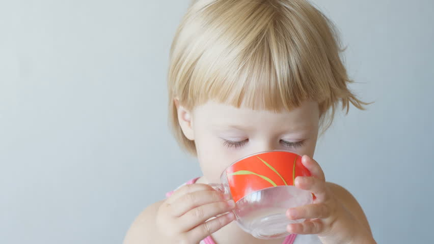 Little blonde girl drinks milk from a red glass at home