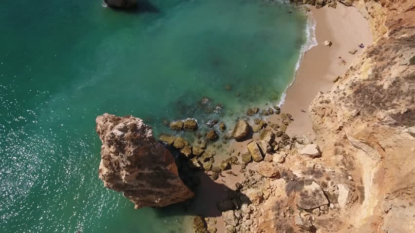 Flying over one of the most beautiful beaches - Praia Da Marinha (Marinha Beach) in Algarve, Portugal. Beautiful cliffs & rock formations. It is a very stable, 4K resolution footage taken by a drone.