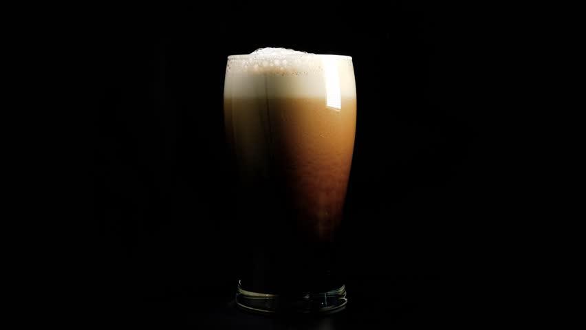 A pint of dark beer foam beautifully against black background