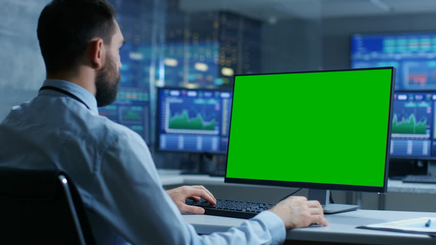 Over the Shoulder View of Stock Market Trader Working on a Computer with Isolated Mock-up Green Screen. In the Background Monitors Show Stock Ticker Numbers and Graphs. Shot on RED EPIC-W 8K Camera. | Shutterstock HD Video #32305207