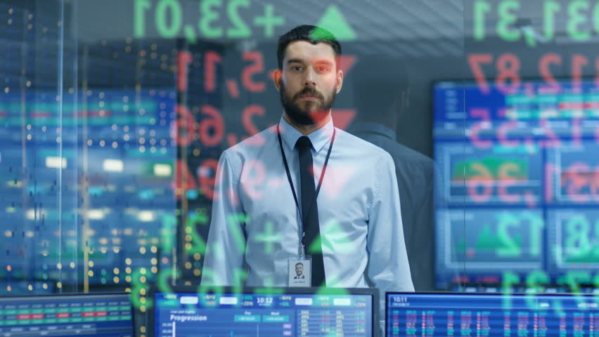 Stock Market Top Trader Looks at Projected Ticker Numbers and Graphs Running, Analysing Data to Make Best Sell. Behind Him Room Full of Screens and Statistics. Shot on RED EPIC-W 8K Helium Camera.