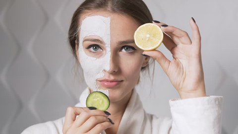 Smiling girl having fun with cucumber and lemon while applying a clay face mask, isolated shot in the white background