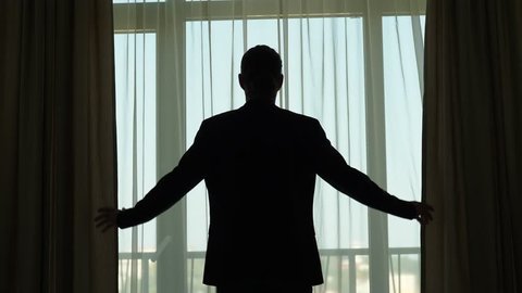 Man in stand against large window, stretch out hands and shut curtains, close sunny day view. Half length shot, black silhouette of guy wearing casual suit
