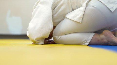 in uniform sitting on tatami of martial arts.