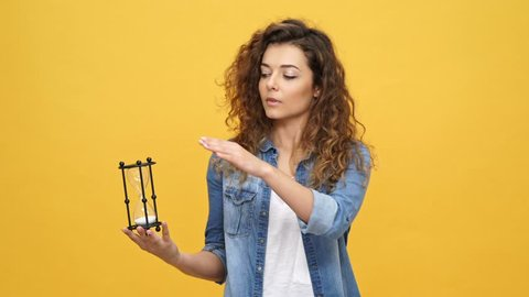 Young curly woman in denim shirt turns the hourglass and pointing at camera over yellow background