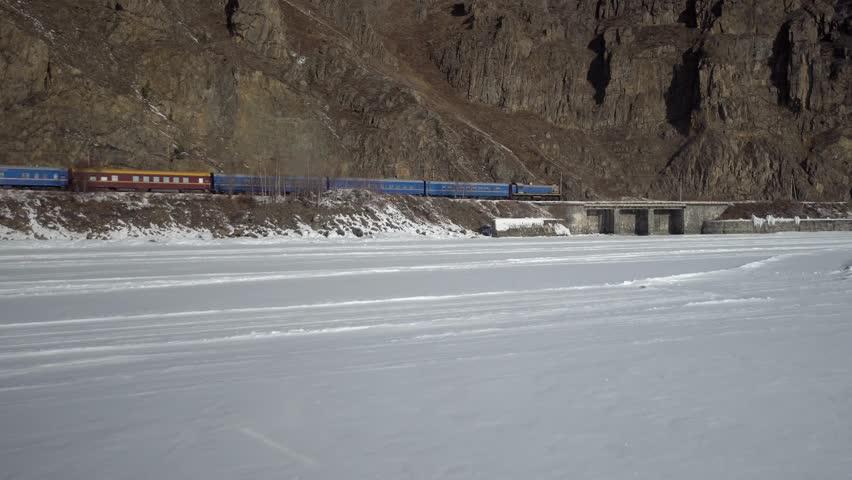 Luxury train blue ride near Baikal lake Transbaikal Trans-Siberian railway. Winter snow ice. High rocks at background. Gimbal follow 4k footage