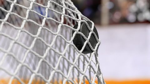 Hockey puck flies into the net on a hockey boards with a yellow stripe. In slow motion. Close-up (4k, 3840x2160, ultra high definition)