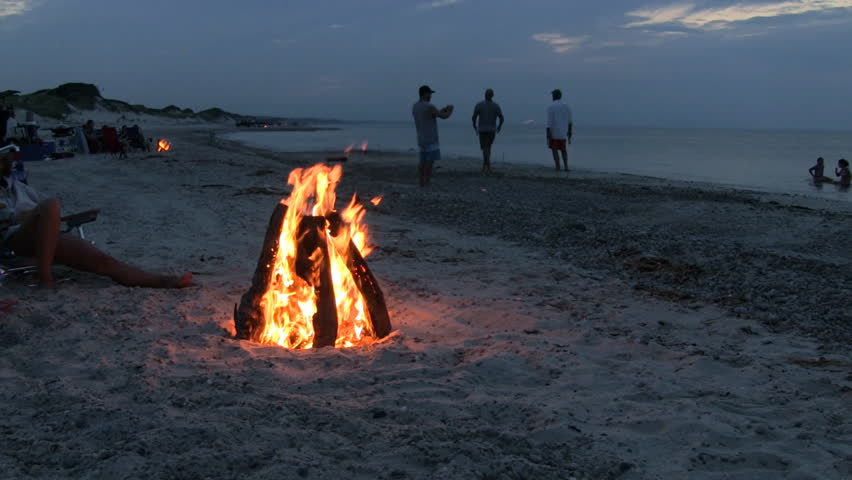 Summertime beach bonfire get together playing horseshoes in the sand and playing in the water at dusk | Shutterstock HD Video #32411317