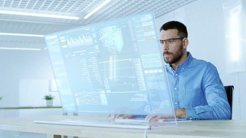 In the Futuristic Laboratory Creative Engineer Works on the Transparent Computer Display. Screen Shows Interactive User Interface with Neural Network, Artificial Intelligence Prototype. 4K UHD.