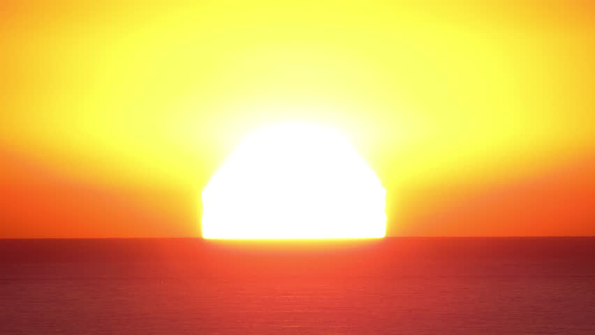 Time lapse of the large golden sun setting into the horizon above the ocean water with the rare green flash at the end